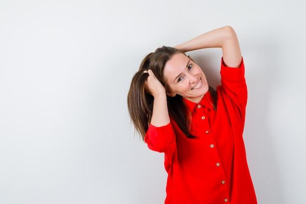 Młoda kobieta w czerwonej bluzce trzymając włosy rękami i patrząc wesoły, widok z przodu.