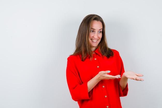 Młoda kobieta w czerwonej bluzce udaje, że coś pokazuje i wygląda na zadowoloną, widok z przodu.
