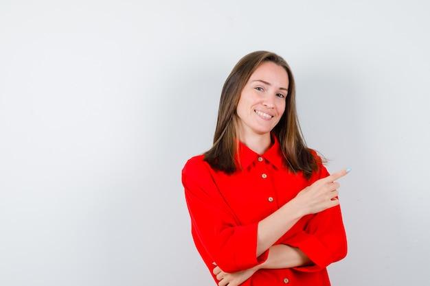 Młoda kobieta w czerwonej bluzce wskazuje w górę i wygląda na szczęśliwego, widok z przodu.
