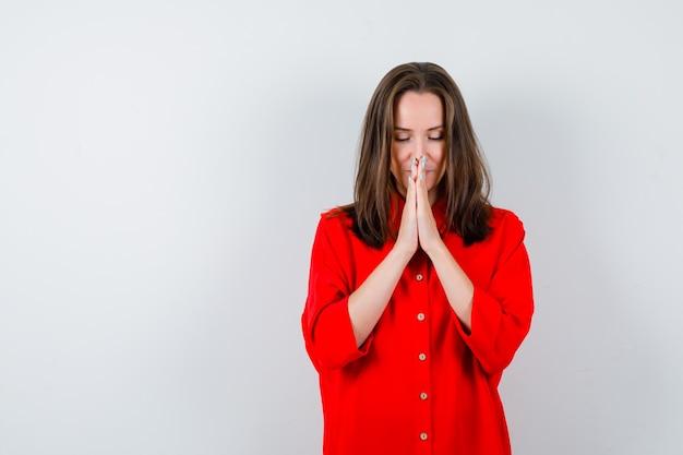 Młoda kobieta w czerwonej bluzce z rękami w geście modlitwy i patrząc z nadzieją, widok z przodu.