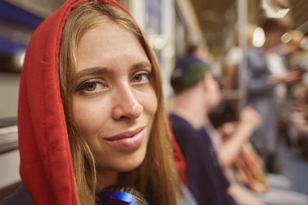 Młoda kobieta w czerwonej bluzie z kapturem na tle pasażerów w samochodzie pociągu w metrze w godzinach szczytu.
