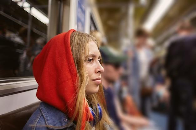 Młoda kobieta w czerwonej bluzie z kapturem w samochodzie pociągu w metrze.