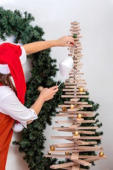 Młoda kobieta w czerwonej czapce karła ozdabia stylizowaną choinkę maskami na twarz, koronawirusem i świąteczną koncepcją