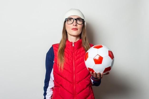Młoda kobieta w czerwonej kamizelce, kapeluszu i okularach trzyma piłkę nożną i patrzy na jasną ścianę