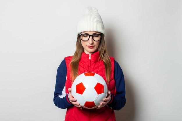 Młoda kobieta w czerwonej kamizelce, kapeluszu i okularach trzyma piłkę nożną i patrzy w bok