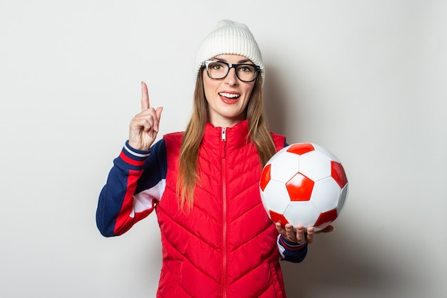 Młoda kobieta w czerwonej kamizelce, kapeluszu i okularach trzyma piłkę nożną i wskazuje palcem w górę