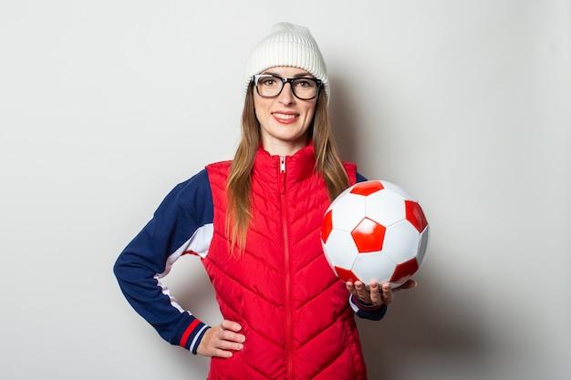 Młoda kobieta w czerwonej kamizelce, kapeluszu i okularach trzyma piłkę nożną przed jasną ścianą