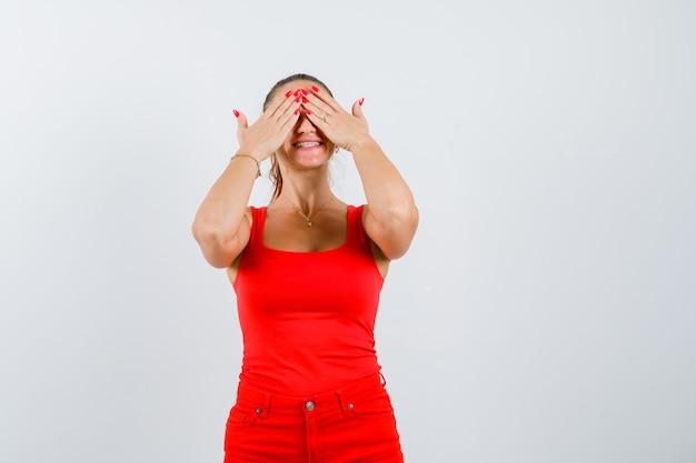 Młoda kobieta w czerwonej koszulce bez rękawów, spodnie zakrywające oczy dłońmi i wyglądająca na szczęśliwą, widok z przodu.