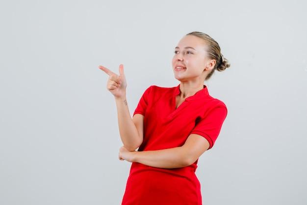 Młoda kobieta w czerwonej koszulce pokazuje gest pistoletu i szuka wesoło
