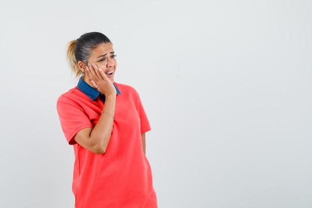 Młoda kobieta w czerwonej koszulce, trzymając dłoń na policzkach, o bólu zęba i ponuro, widok z przodu.