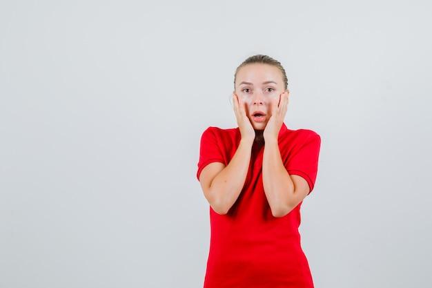 Młoda kobieta w czerwonej koszulce, trzymając się za ręce na policzkach i patrząc przestraszony