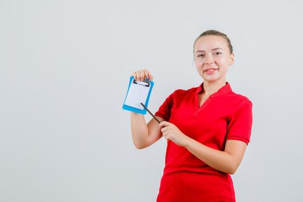 Młoda kobieta w czerwonej koszulce, wskazując ołówkiem w schowku i patrząc wesoło
