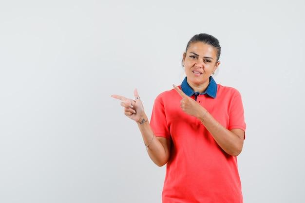 Młoda kobieta w czerwonej koszulce, wskazująca w lewo palcami wskazującymi i niezadowolona, widok z przodu.