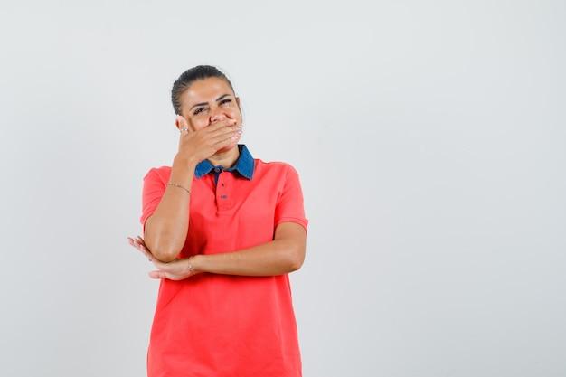 Młoda kobieta w czerwonej koszulce zakrywającej usta ręką i patrząc ładny, przedni widok.