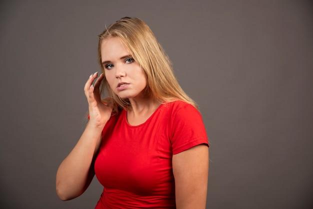 Młoda kobieta w czerwonej koszuli pozowanie na czarnej ścianie.
