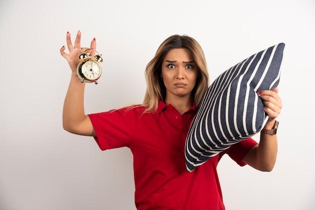 Młoda kobieta w czerwonej krótkiej trzymającej poduszce i zegarze