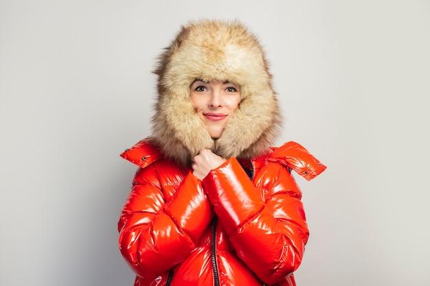 Młoda kobieta w czerwonej kurtce i futrzanym kapeluszu na białym tle