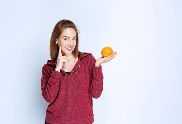 Młoda kobieta w czerwonej kurtce trzyma pomarańczę i wygląda na zamyśloną