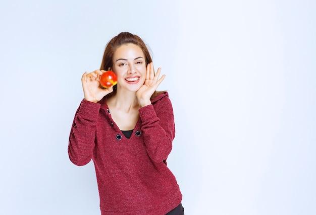 Młoda kobieta w czerwonej kurtce trzymająca czerwone jabłko