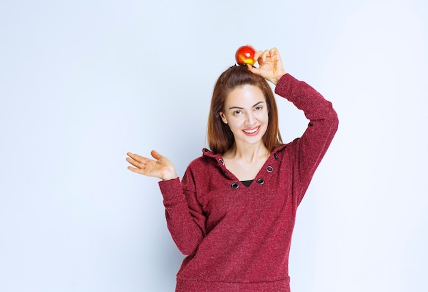 Młoda kobieta w czerwonej kurtce trzymająca nad głową czerwone jabłko