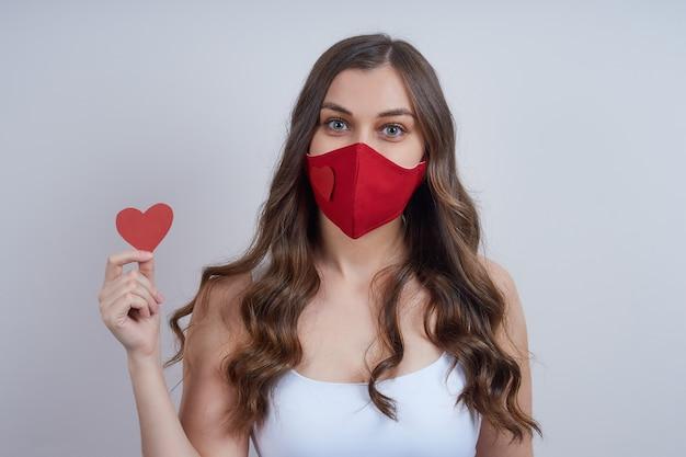 Młoda kobieta w czerwonej masce ochronnej z papierowym sercem w dłoni