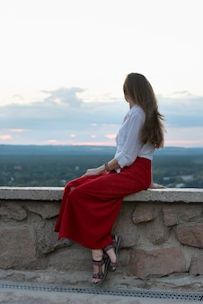 Młoda kobieta w czerwonej spódnicy siedzi na tarasie widokowym z widokiem na przyrodę. rama pionowa.