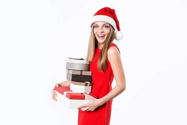 Młoda kobieta w czerwonej sukience i santa hat trzyma pudełka