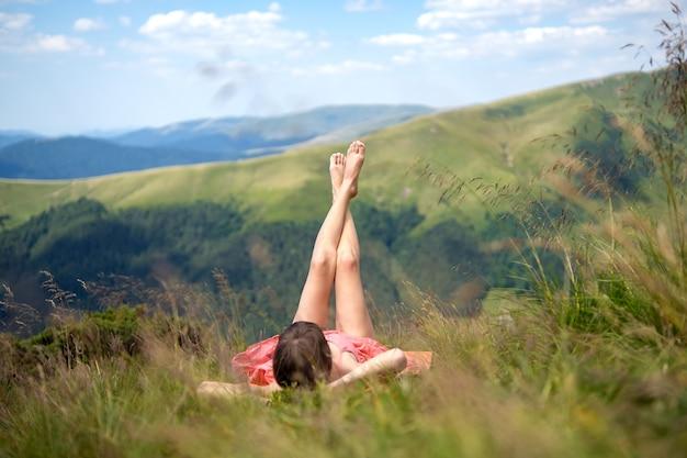 Młoda kobieta w czerwonej sukience leżącej na zielonym trawiastym polu odpoczynku w słoneczny dzień w górach latem z widokiem na przyrodę.