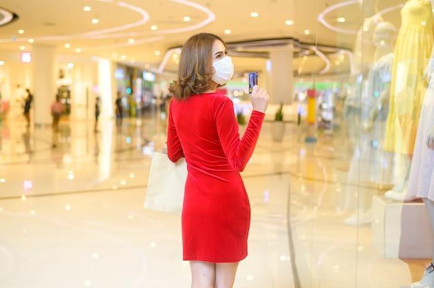 Młoda kobieta w czerwonej sukience nosząca maskę ochronną w centrum handlowym, robiąca zakupy w ramach koncepcji pandemii covid-19.