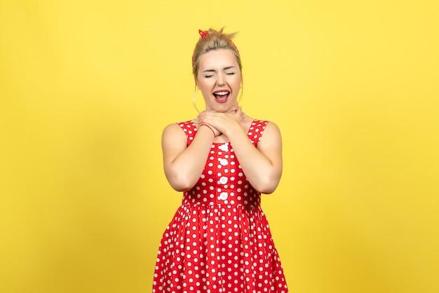 Młoda kobieta w czerwonej sukience w kropki, krztusząc się na żółto