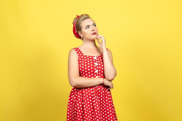 Młoda kobieta w czerwonej sukience w kropki pozowanie i myśli na żółto