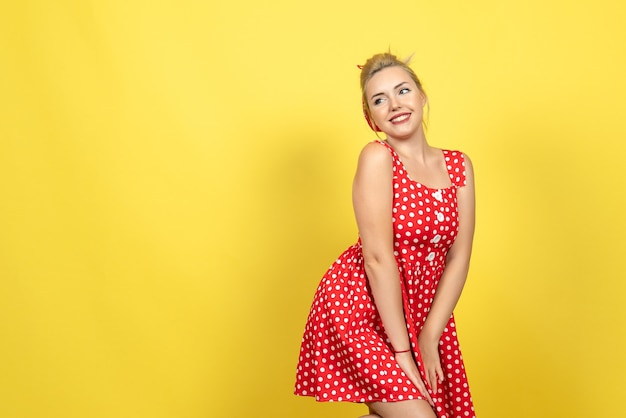 Młoda kobieta w czerwonej sukience w kropki pozowanie na żółto