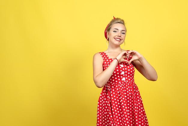 Młoda kobieta w czerwonej sukience w kropki pozowanie z uśmiechem na żółto