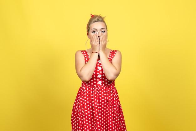 Młoda kobieta w czerwonej sukience w kropki zakrywającej twarz na żółto