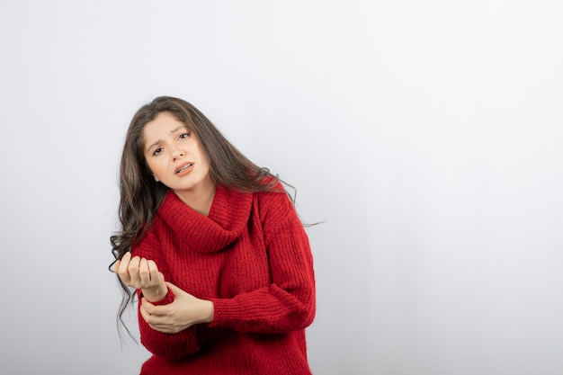 Młoda kobieta w czerwonym ciepłym swetrze cierpi na ból w ramieniu.