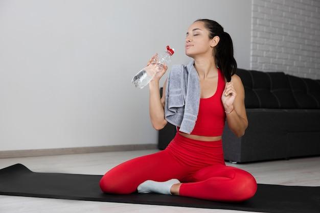 Młoda kobieta w czerwonym dresie robi ćwiczenia lub jogę w domu. siedząc samotnie na macie i pozując z butelką wody. picie lub nawadnianie po treningu. samo dbanie o dobre samopoczucie.