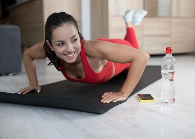 Młoda kobieta w czerwonym dresie robi ćwiczenia lub jogę w domu. wesoła pozytywna i szczęśliwa dziewczyna stoi na pozycji deski na kolanach. oprzyj się na rękach i spoglądaj w bok. telefon i butelka wody obok.