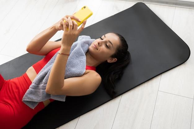 Młoda kobieta w czerwonym dresie robi ćwiczenia lub jogę w domu