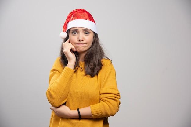 Młoda kobieta w czerwonym kapeluszu świętego mikołaja pozowanie na białej ścianie.