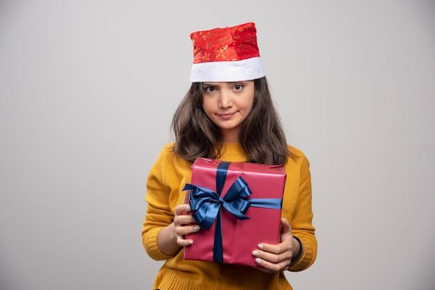 Młoda kobieta w czerwonym kapeluszu świętego mikołaja z prezentem bożonarodzeniowym.