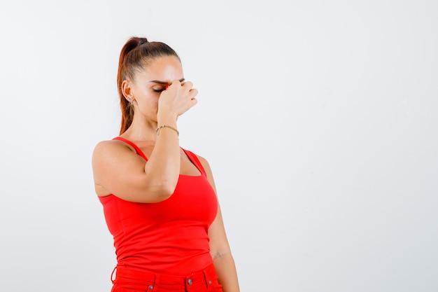 Młoda kobieta w czerwonym podkoszulku, spodniach masuje mostek nosa i wygląda na wyczerpaną, widok z przodu.