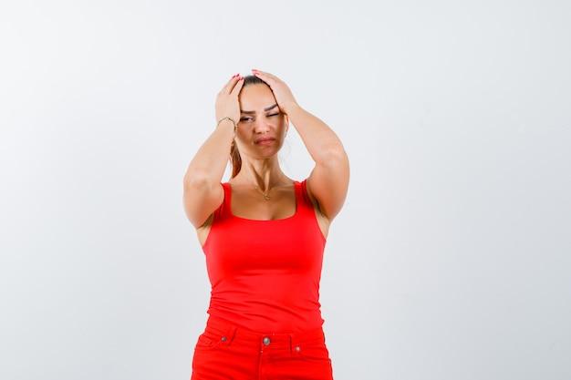 Młoda kobieta w czerwonym podkoszulku, spodnie trzymając głowę rękami i patrząc zdenerwowany, widok z przodu.