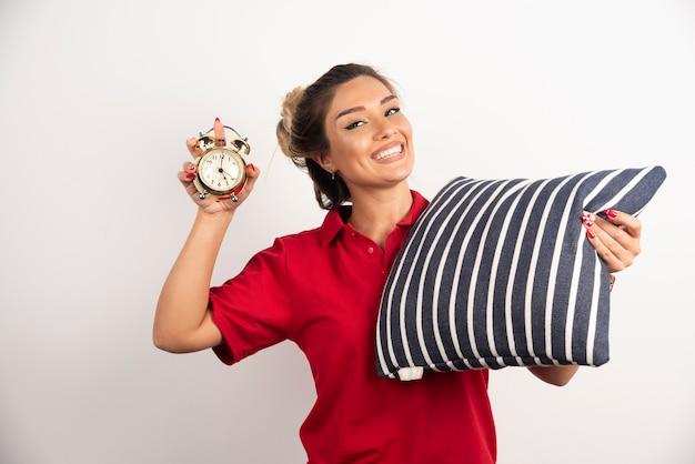 Młoda kobieta w czerwonym skrócie pokazując budzik i trzymając poduszkę.