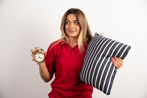 Młoda kobieta w czerwonym spodenku z poduszką i zegarem