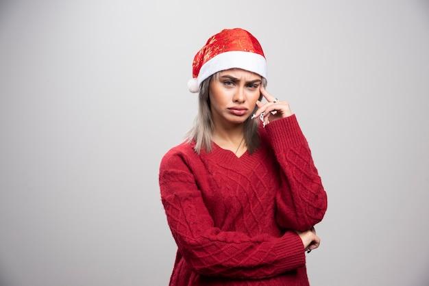 Młoda kobieta w czerwonym swetrze myśli intensywnie.