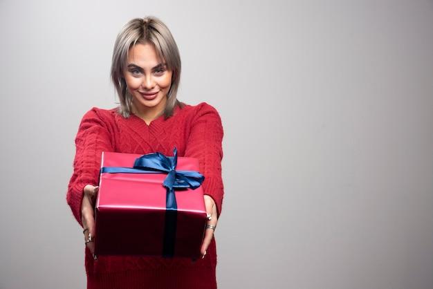 Młoda kobieta w czerwonym swetrze oferuje prezent na boże narodzenie.