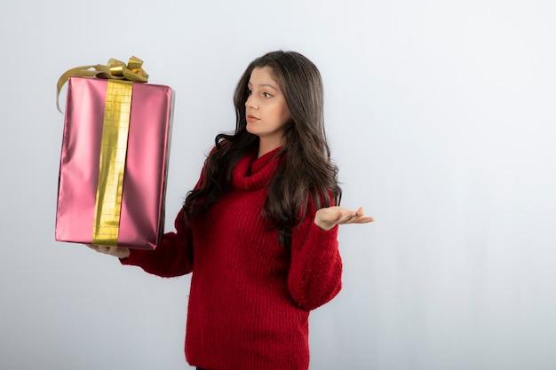 Młoda kobieta w czerwonym swetrze patrząc na prezenty świąteczne.