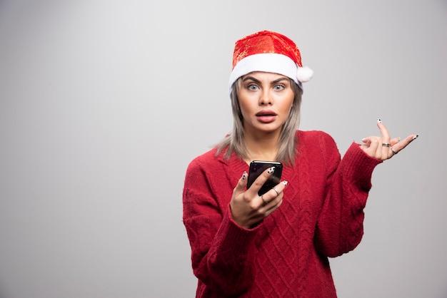Młoda kobieta w czerwonym swetrze trzymając telefon i patrząc na kamery.