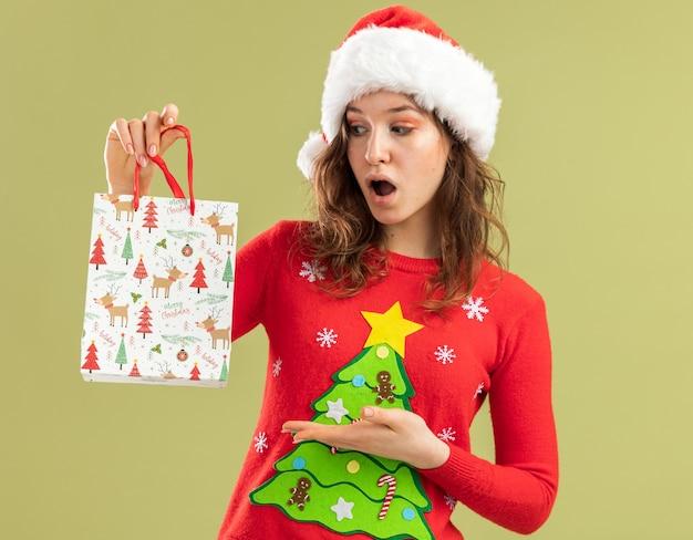 Młoda kobieta w czerwonym świątecznym swetrze i mikołajowym kapeluszu trzymająca papierową torbę z prezentami świątecznymi prezentująca ręką patrząc na torbę zaskoczona stojąca nad zieloną ścianą