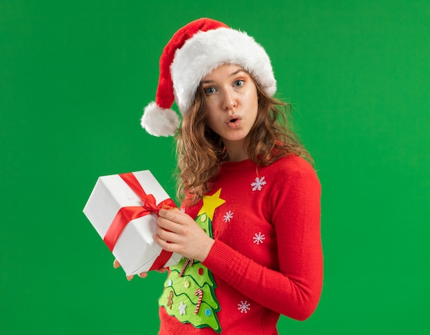 Młoda kobieta w czerwonym świątecznym swetrze i santa hat trzymająca prezent zaskoczona stojąc nad zieloną ścianą